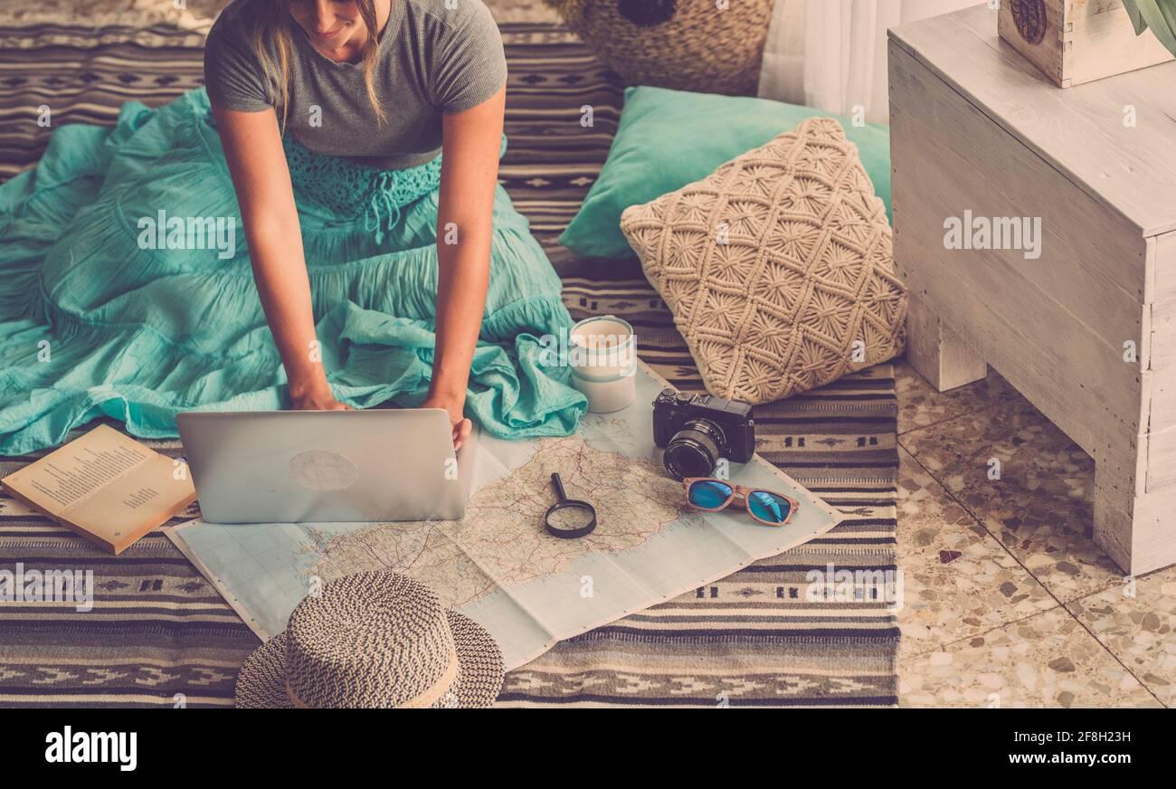 Femme caucasienne planifiant un voyage de vacances avec ordinateur portable et guide de carte à la maison, les femmes planifient les prochaines vacances tout en se relaxant sur l'étage - pr Banque D'Images