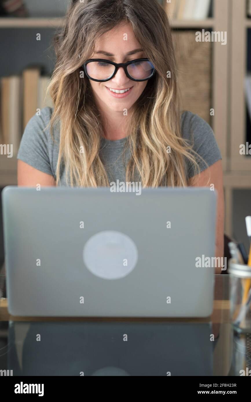 Jolie femme avec des lunettes de travail de lunettes à la maison sur ordinateur portable ordinateur - femmes travaillant intelligemment au bureau regardant le moniteur - mode professionnel Banque D'Images
