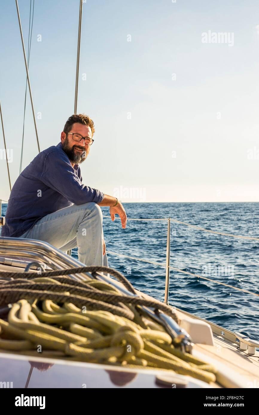 Heureux mature homme beau assis et reposant sur le bateau à voile terrasse en profitant de l'océan bleu voyage aventure seule - gratuit style de vie et personnes gaies o Banque D'Images