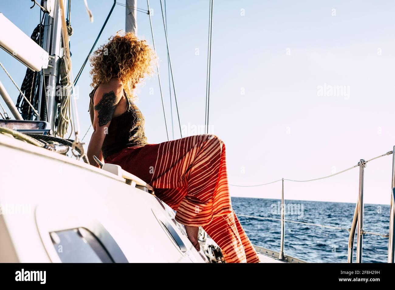 Une jeune femme se détend et fait une excursion en voilier vacances d'été - des femmes assises sur le yacht terrasse regardant l'horizon avec b Banque D'Images