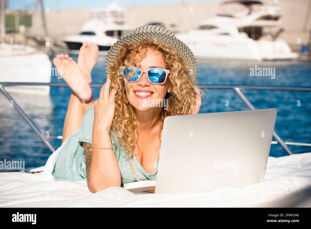 Jeune femme assez adulte sourire et utiliser un ordinateur portable à l'extérieur couchez-vous sur le pont d'un yacht - voyage et vacances d'été style de vie et mod Banque D'Images