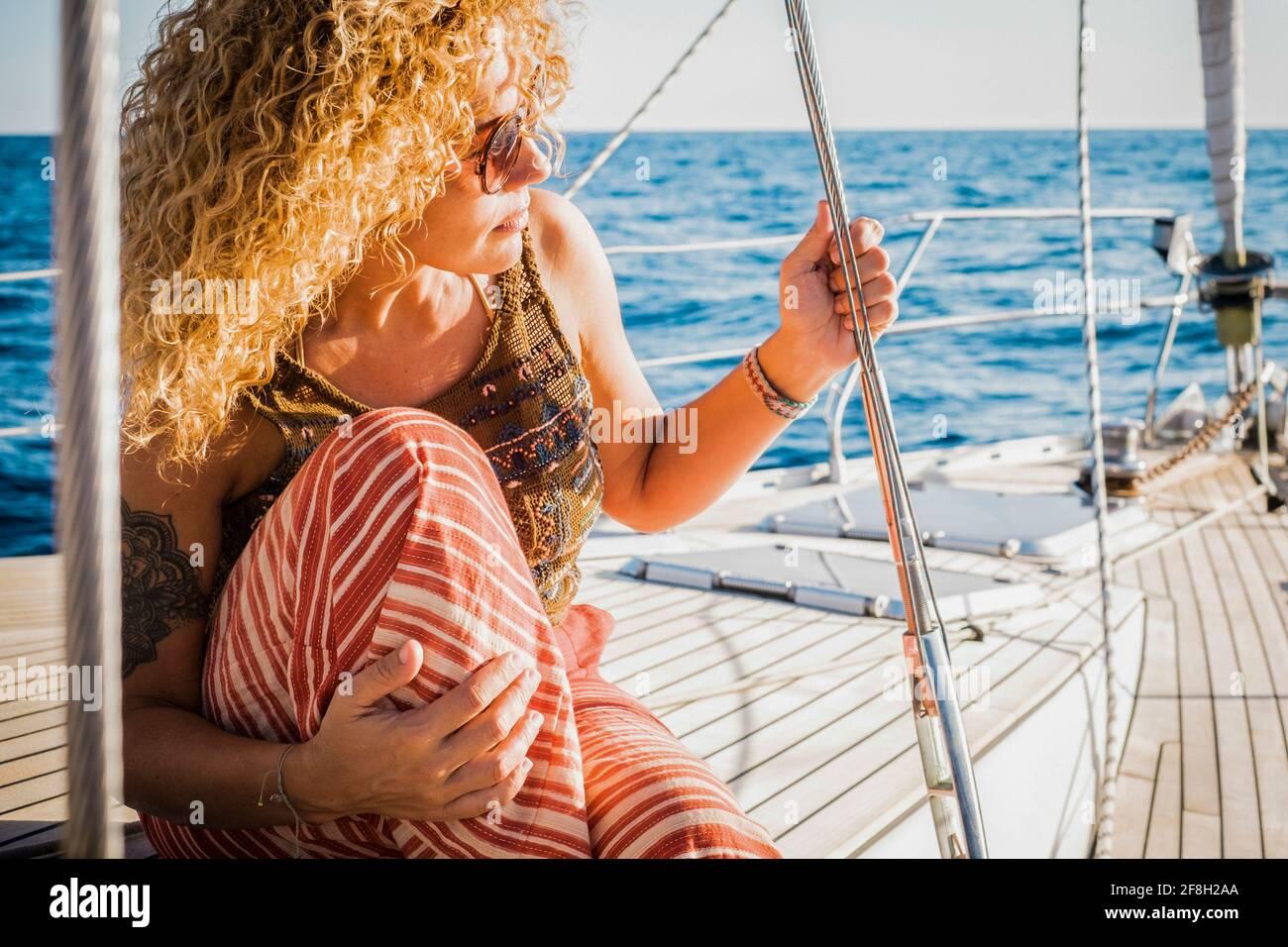 Portrait d'une femme d'âge moyen attrayante assise sur le bois terrasse du yacth appréciant le voyage - concept de style de vie de luxe avec yacht - femme p Banque D'Images