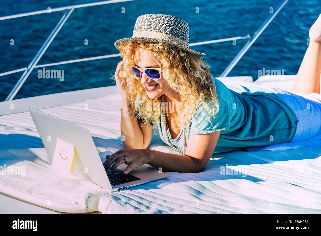 Une femme joyeuse travaille à l'extérieur avec un ordinateur portable un bateau bénéficiant de la liberté et de la connexion internet - concept de personnel et mode de travail intelligent Banque D'Images