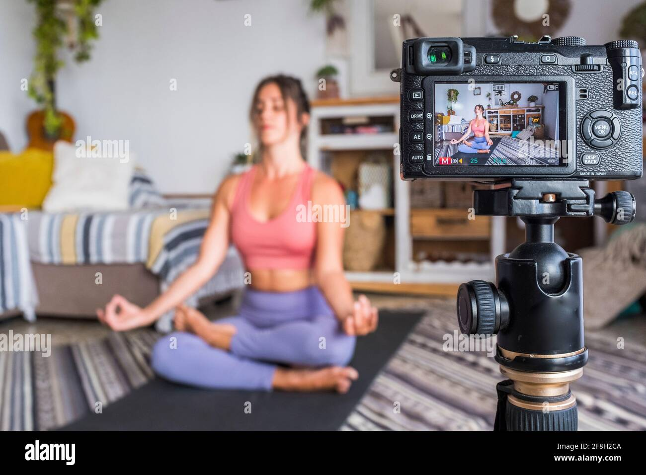 Jeune femme s'exerçant à la maison faisant pilates et l'enregistrement à elle dispose d'un appareil photo numérique pour enseigner l'entraînement et produire du web classe - les affaires du créateur de contenu Banque D'Images