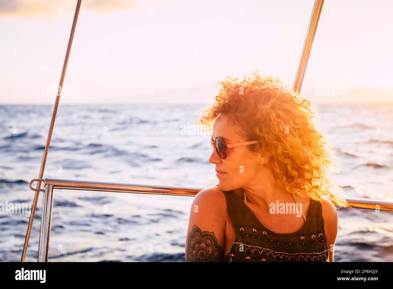 Belle femme profiter du coucher de soleil assis sur le yacht à l'intérieur voyage en mer - portrait des femmes heureux extérieur avec coucher de soleil et océan Banque D'Images