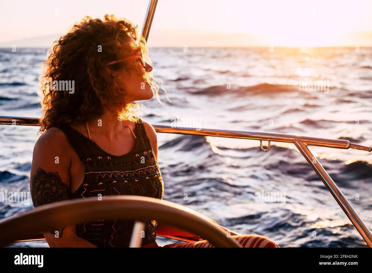 Gaie et attrayante jeune femme blonde adulte sourire et profiter de la excursion assise sur le pont en voilier qui regarde le bleu mer autour - concept de Banque D'Images