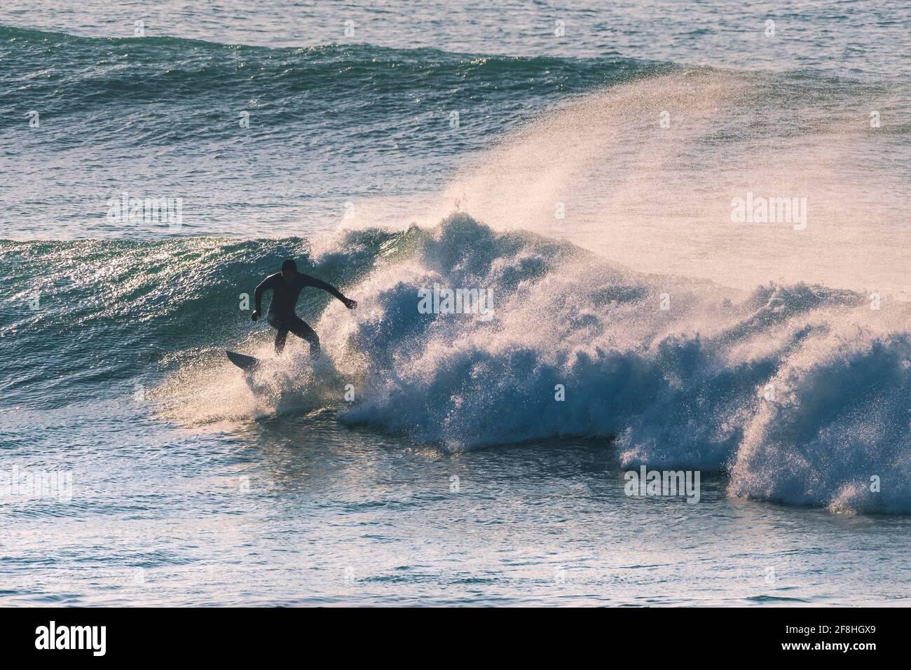 Un surfeur qui fait une vague et silhoueté par la lumière du début de soirée à Fistral à Newquay en Cornouailles. Banque D'Images