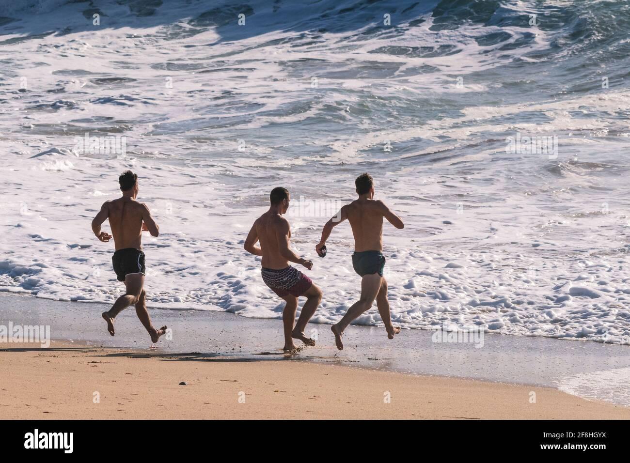 Des vacanciers mâles qui se rendient dans la mer à Fistral Beach à Newquay, en Cornouailles. Banque D'Images
