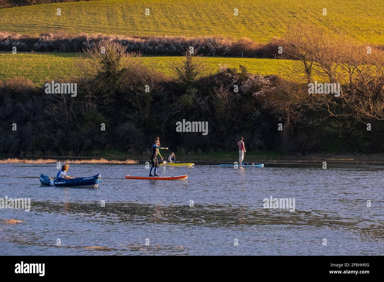 Les gens pagayent sur la rivière Gannel dans des kayaks et sur des pagayboards Stand Up à Newquay, en Cornouailles. Banque D'Images