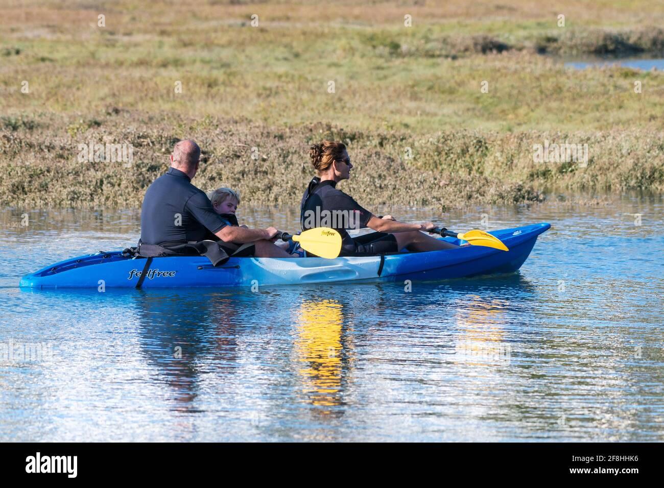 Une famille de vacanciers qui s'amusent à faire du canoë-kayak sur la rivière Gannel à marée haute à Newquay, en Cornouailles. Banque D'Images