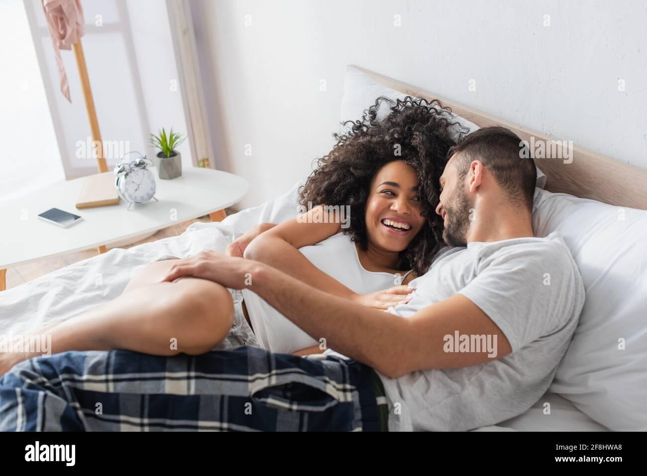 couple interracial gai souriant et allongé sur le lit Banque D'Images