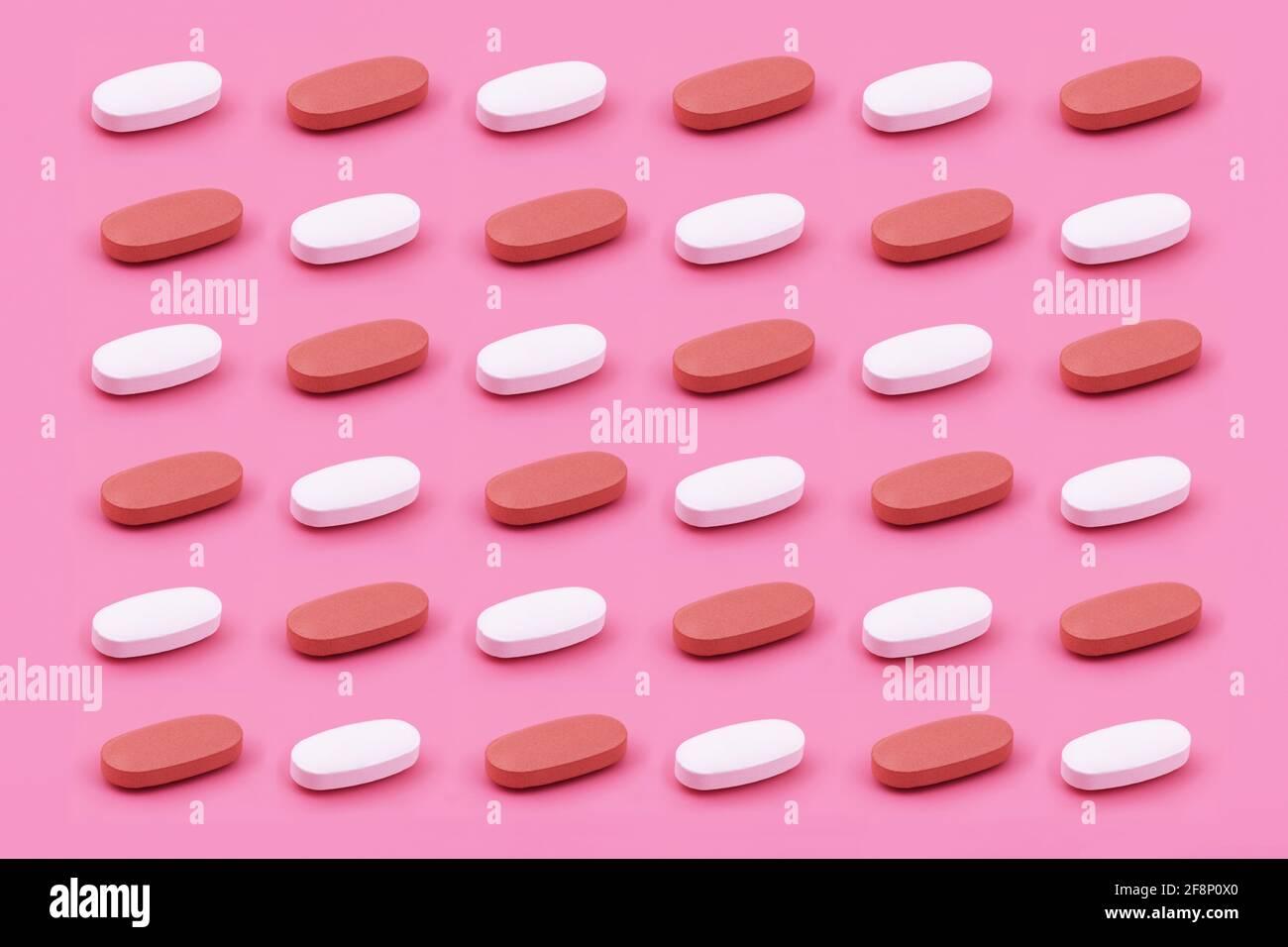 Forme ovale comprimé de médecine pharmaceutique sur fond rose, Medicine concepts créatifs style minimal avec fond de papier coloré Banque D'Images