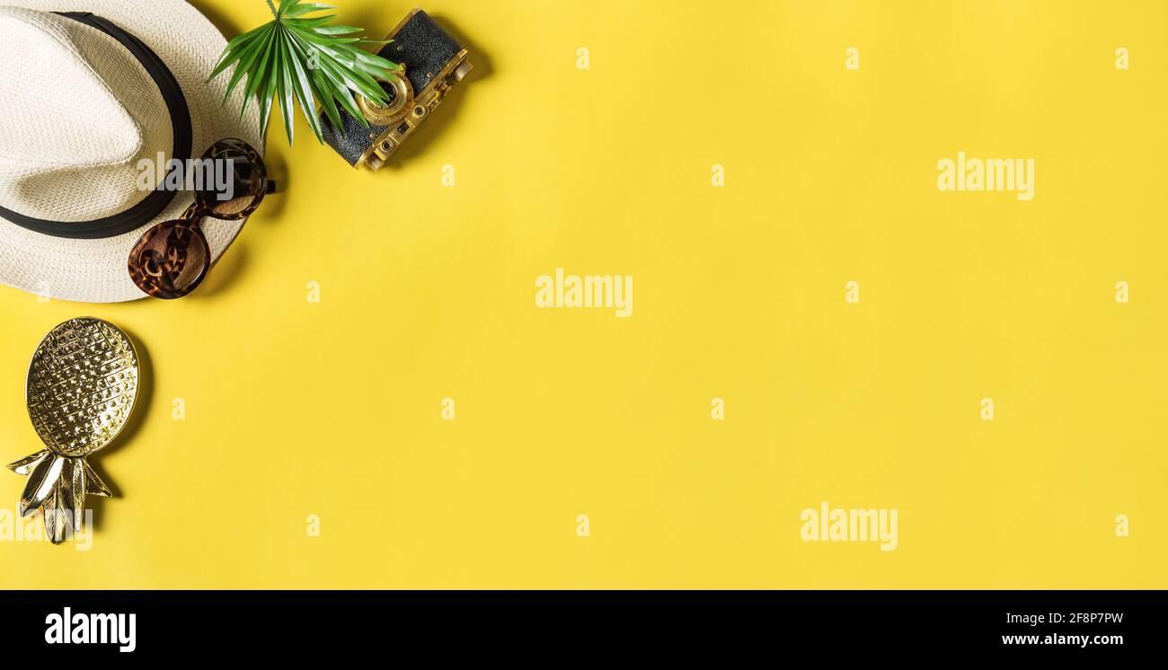Pose à plat de l'appareil de travail. Lunettes de soleil, feuille de palmier, appareil photo, chapeau de paille sur fond jaune Banque D'Images