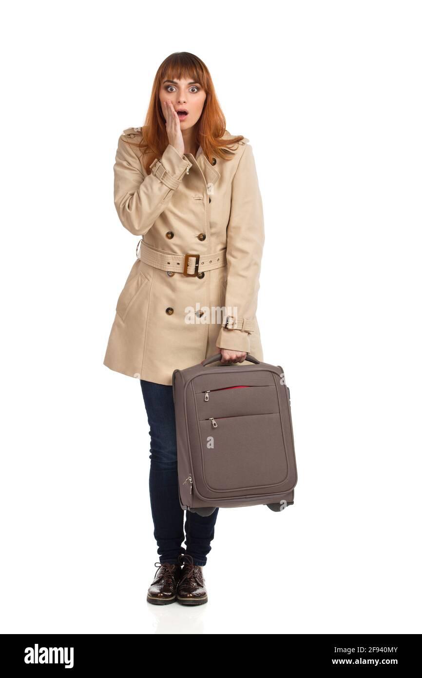 La jeune femme choquée en beige manteau, jeans et chaussures brunes est debout avec une valise et la main sur le menton. Vue avant. Prise de vue en studio pleine longueur isola Banque D'Images