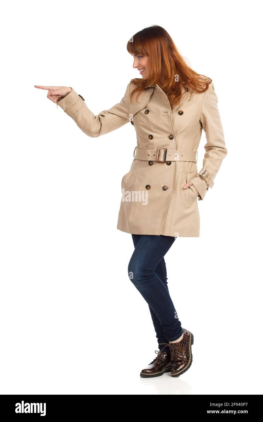 Jeune femme en beige manteau, jeans et chaussures brunes est debout, pointant ou poussant quelque chose. Vue latérale. Prise de vue en studio sur toute la longueur isolée sur blanc. Banque D'Images