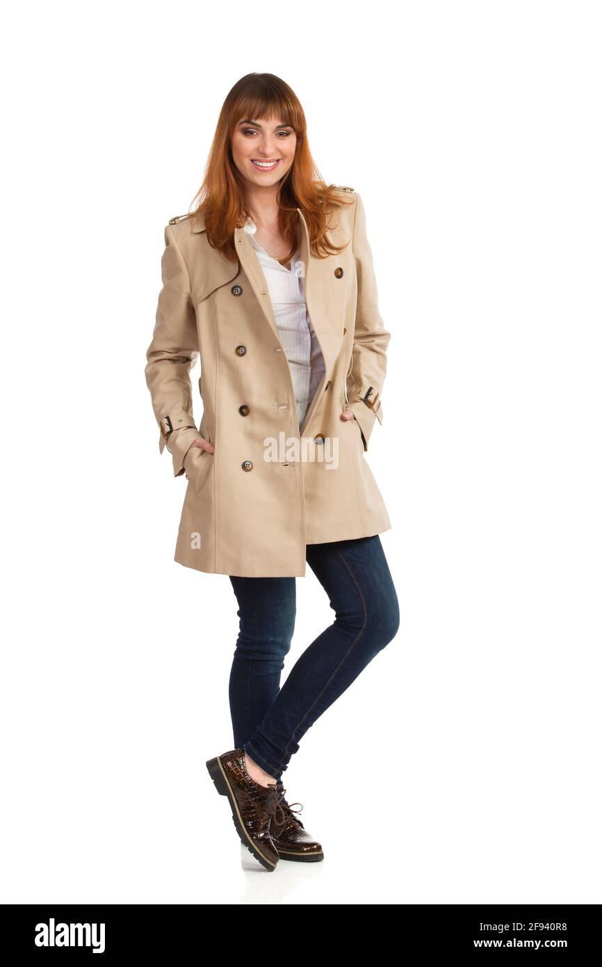 Jeune femme en beige manteau, jeans et chaussures marron est debout avec les mains dans les poches, souriant et regardant l'appareil photo. Vue avant. Prise de vue en studio Banque D'Images
