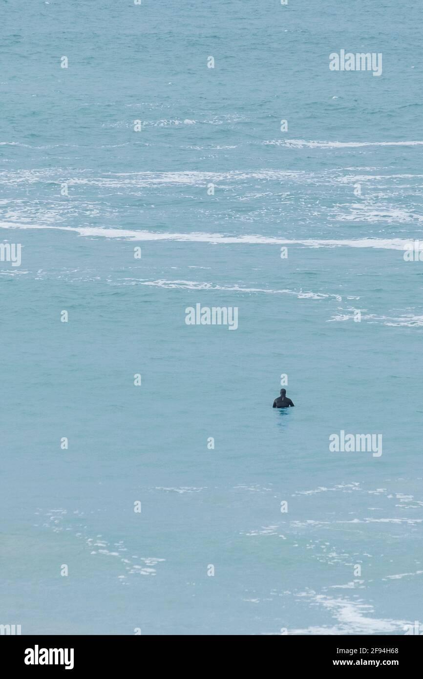 Un surfeur qui attend dans une mer calme pour une vague dans la baie de Fistral à Newquay, en Cornouailles. Banque D'Images