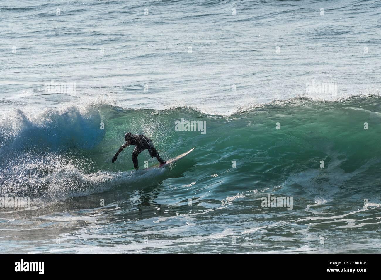 Un surfeur à cheval sur une vague dans la baie de Fistral à Newquay en Cornwall. Banque D'Images