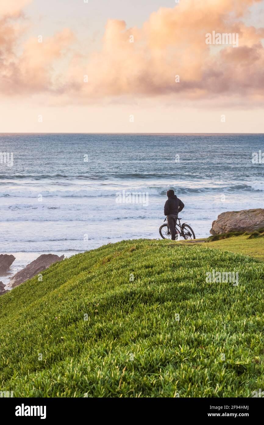 Un cycliste debout sur le promontoire qui regarde à la lumière du soleil en fin de soirée à Newquay, dans les Cornouailles. Banque D'Images