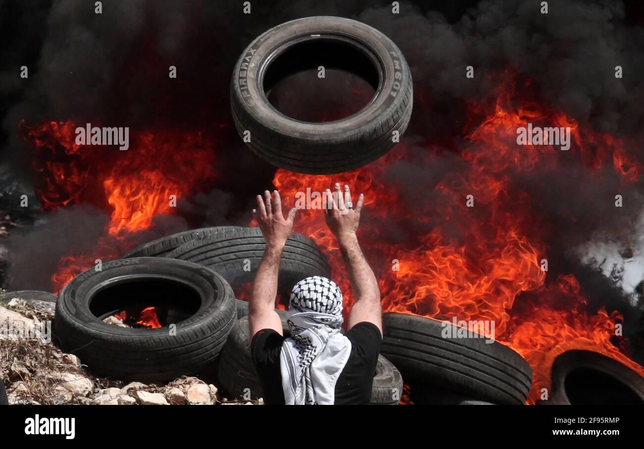 Naplouse. 16 avril 2021. Un manifestant palestinien jette un pneu de voiture au feu lors d'affrontements après une protestation contre l'expansion des colonies juives dans le village de Kufr Qadoom près de la ville de Naplouse, en Cisjordanie, le 16 avril 2021. Crédit: Nidal Eshtayeh/Xinhua/Alamy Live News Banque D'Images
