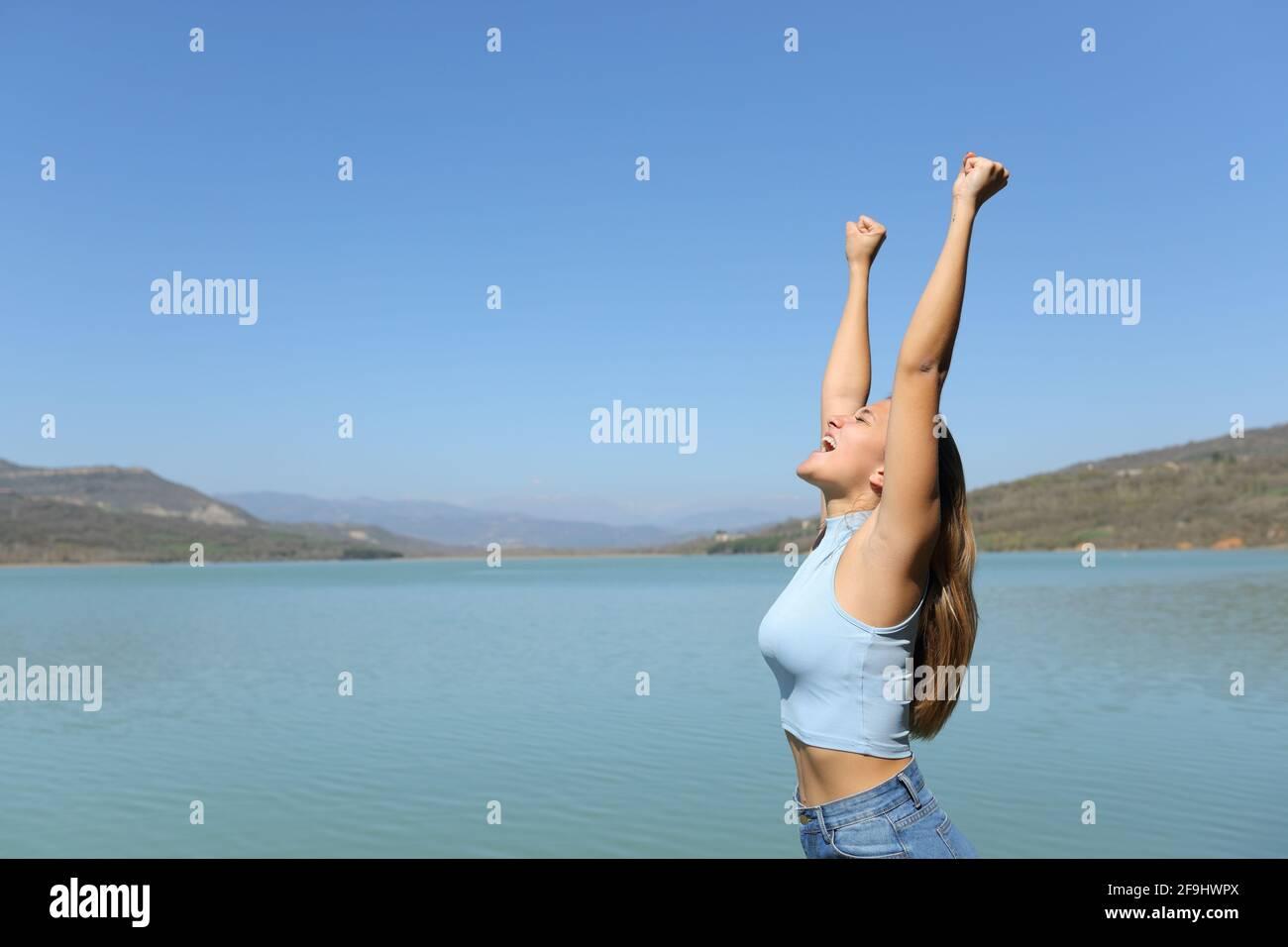 Profil d'une femme excitée célébrant des vacances dans un lac Banque D'Images