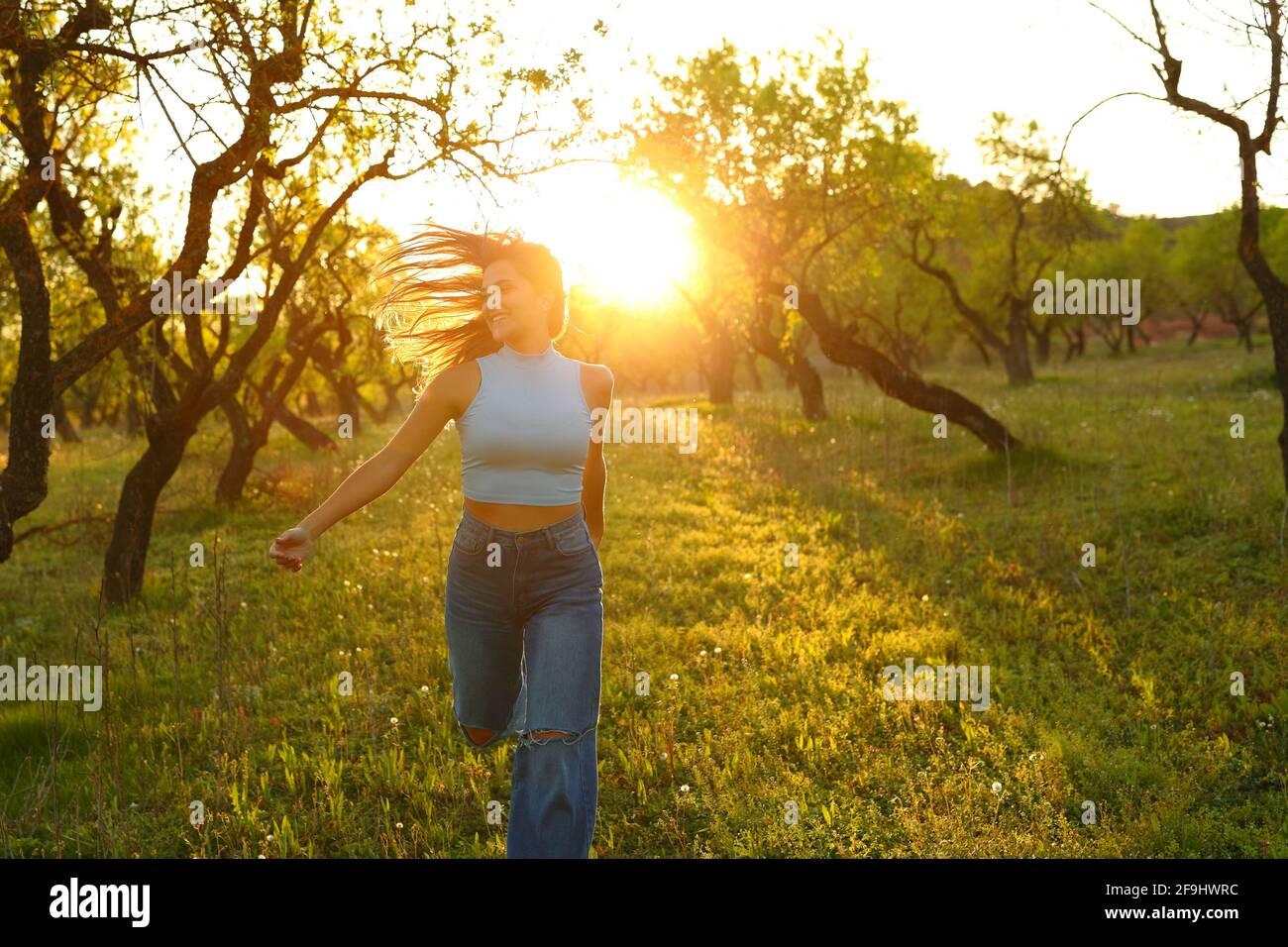 Vue avant d'une femme heureuse qui court vers l'appareil photo à coucher de soleil dans un champ Banque D'Images