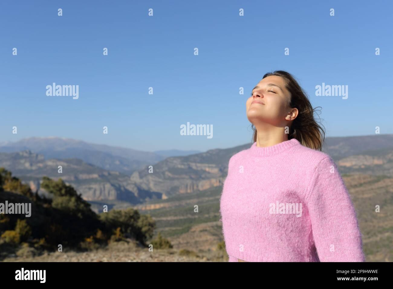 Femme détendue en rose respirant de l'air frais dans la montagne Banque D'Images