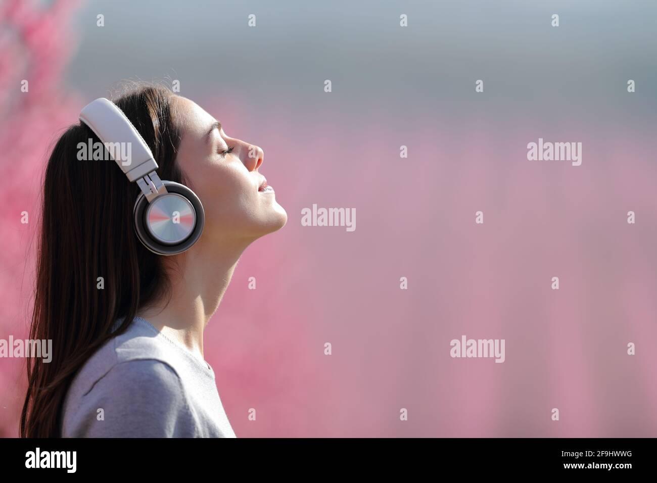 Profil d'une femme qui médite l'écoute audio sur un casque sans fil dans un champ rose Banque D'Images
