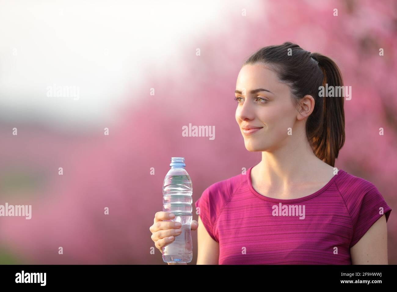 Un coureur satisfait s'éloigne de la bouteille d'eau après l'exercice un champ rose Banque D'Images