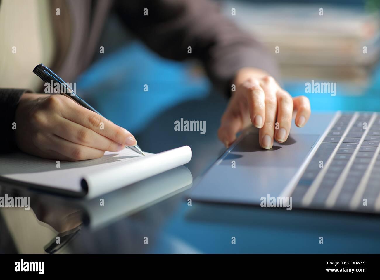 Gros plan d'une main de femme prenant des notes sur l'ordinateur portable utilisation d'un ordinateur portable la nuit à la maison Banque D'Images