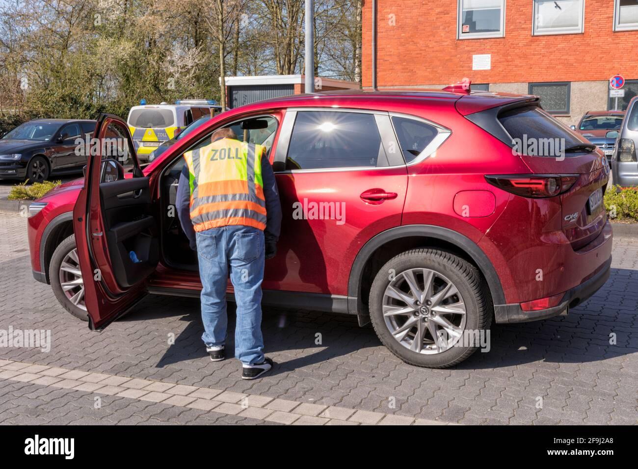 Un fonctionnaire des douanes allemand en civil, portant un gilet d'avertissement, examinant une voiture. Banque D'Images