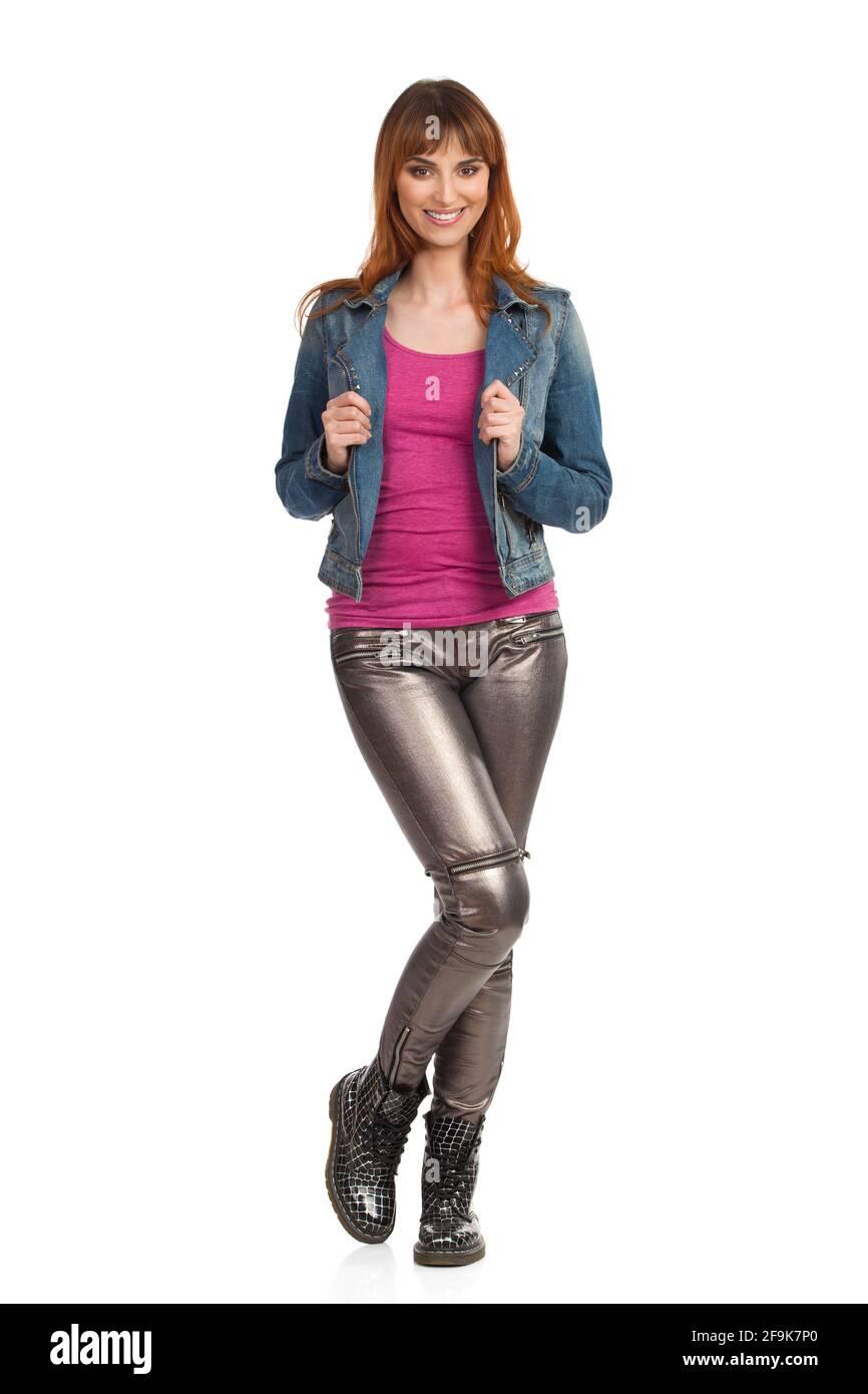 Une jeune femme souriante pose dans une veste de Jean, un pantalon brillant et des baskets. Vue avant. Prise de vue en studio sur toute la longueur isolée sur blanc. Banque D'Images