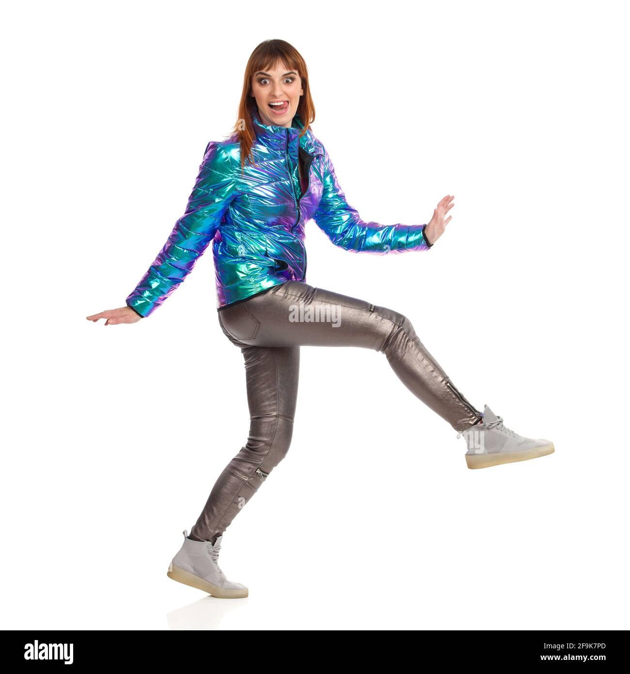 Drôle de jeune femme dans la veste en duvet vibrante, le pantalon brillant et les baskets marche et dépasse la langue. Vue latérale. Prise de vue en studio sur toute la longueur isolée sur Banque D'Images