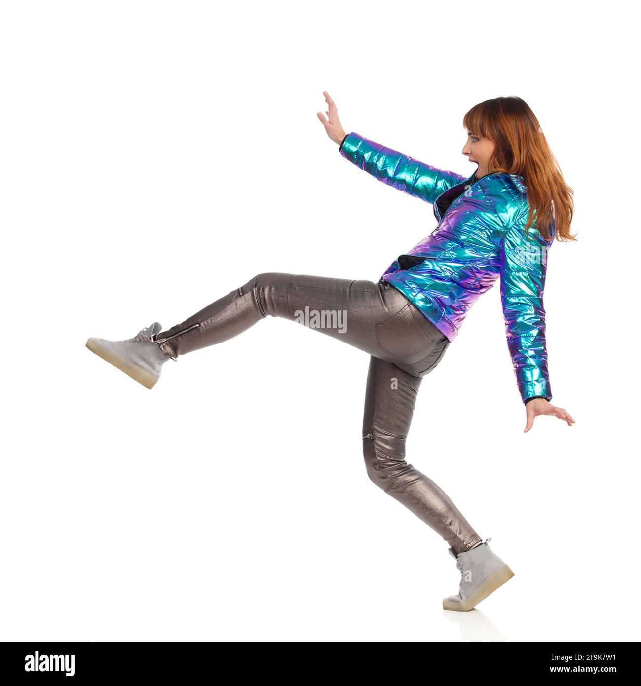 Drôle de jeune femme en veste de duvet, pantalon brillant et baskets est en train de faire un grand pas et crier. Vue latérale. Prise de vue en studio sur toute la longueur isolée sur W Banque D'Images