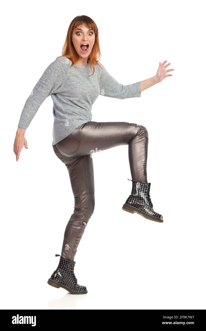 La jeune femme açée dans un chemisier gris, un pantalon brillant et des bottes noires marche, regarde l'appareil photo et crie. Vue latérale. Prise de vue en studio pleine longueur isolée Banque D'Images