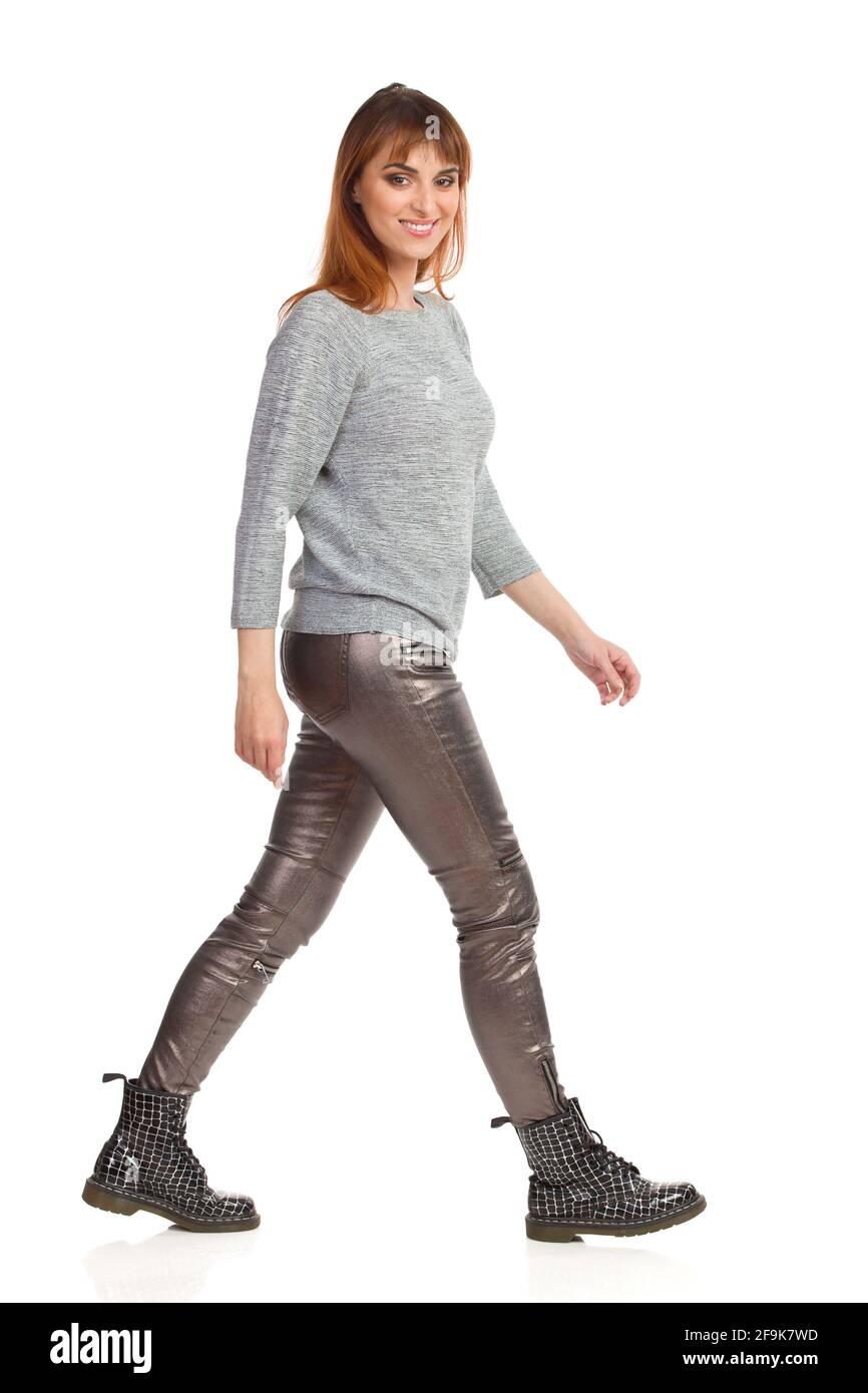 Une jeune femme en blouse grise, pantalon brillant et bottes noires marche, regarde l'appareil photo et sourit. Vue latérale. Prise de vue en studio sur toute la longueur isolée sur le coup Banque D'Images