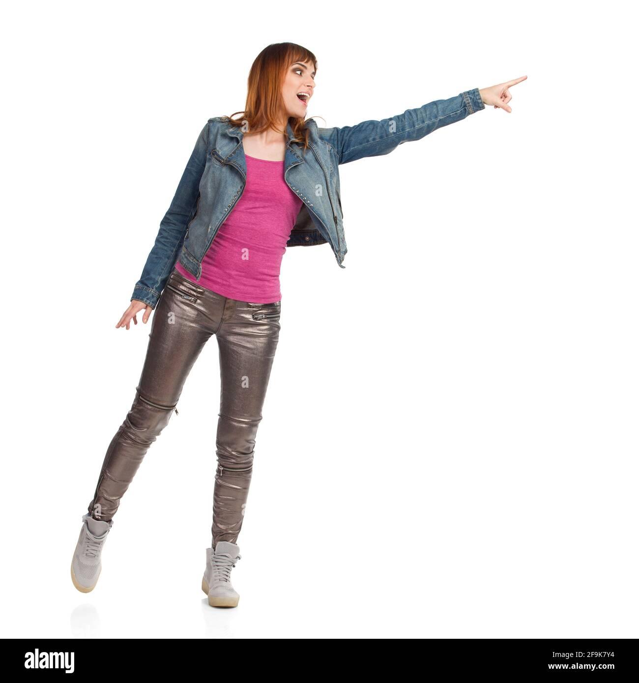Rire jeune femme en veste de Jean, pantalon brillant et baskets essaie de toucher quelque chose. Prise de vue en studio sur toute la longueur isolée sur blanc. Banque D'Images