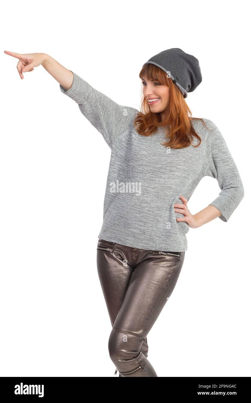 Jeune femme en blouse grise, pantalon brillant et casquette d'hiver est pointant et riant. Trois quarts de longueur en studio prises isolées sur blanc. Banque D'Images
