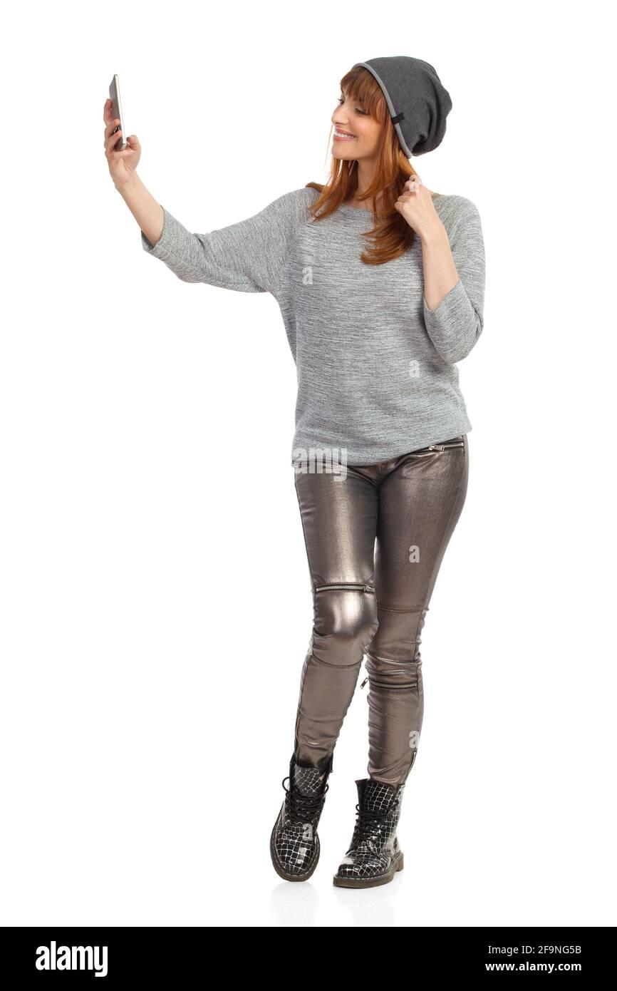 Jeune femme décontractée en blouse grise, pantalon brillant, bottes noires et casquette d'hiver tient le téléphone, parle un selfie et sourire. Prise de vue en studio Banque D'Images