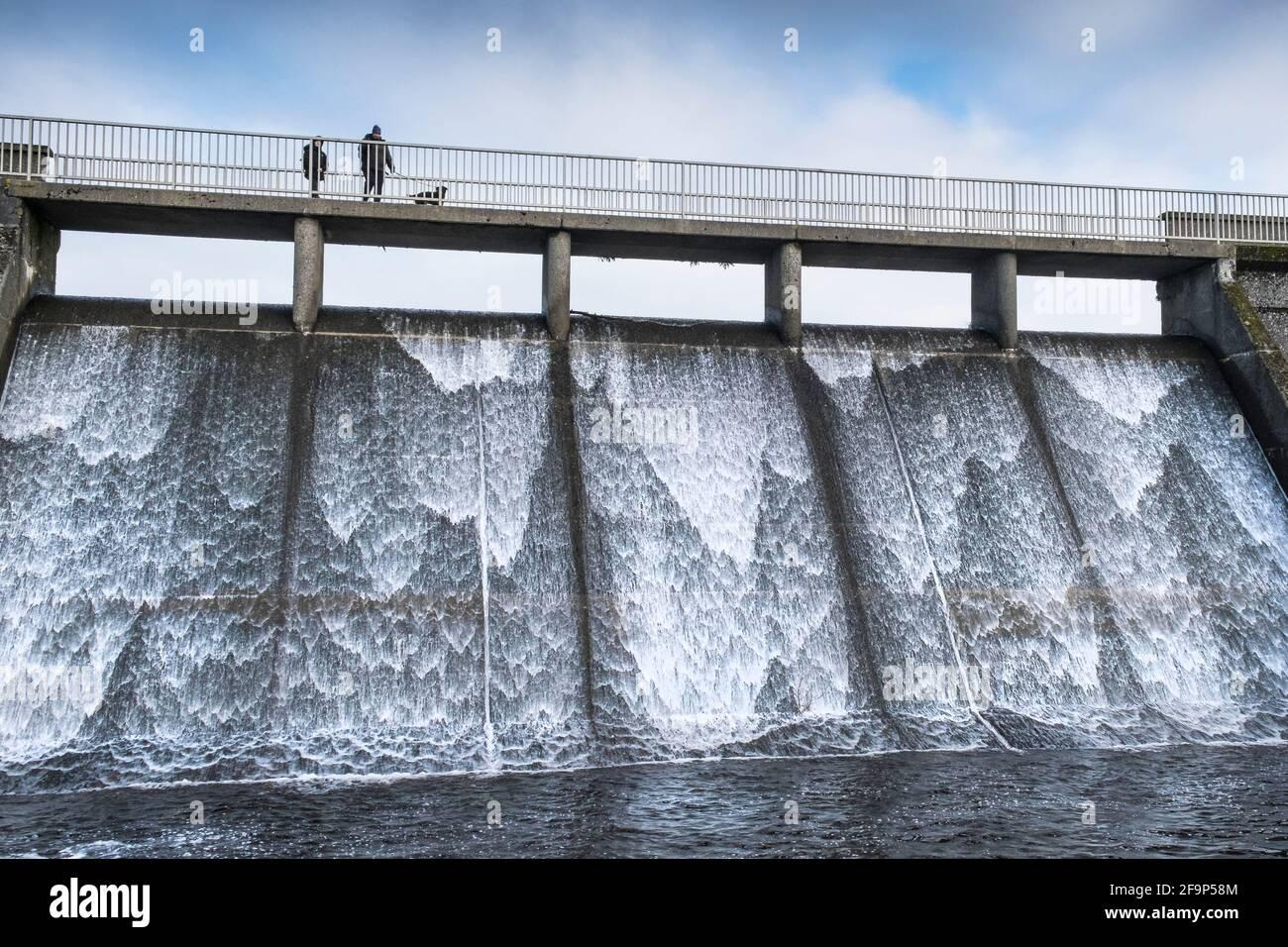 Personnes sur la passerelle au-dessus du déversoir de débordement du réservoir Crowdy sur Bodmin Moor dans Cornwall. Banque D'Images