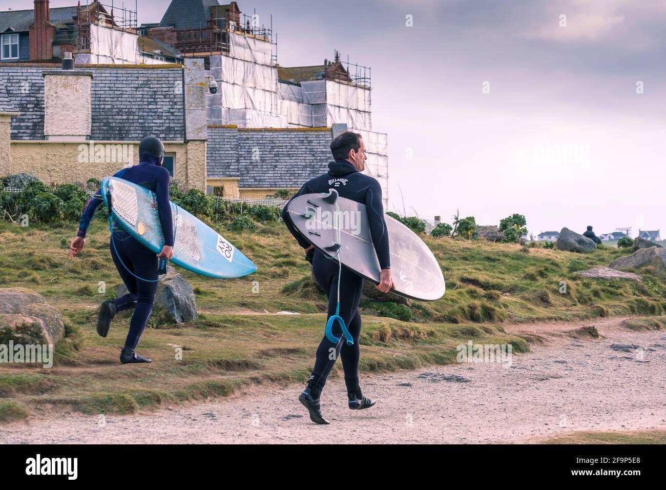 Deux surfeurs passionnés transportant leurs planches de surf et courant le long de la voie côtière sur la côte de Fistral à Newquay en Cornouailles. Banque D'Images