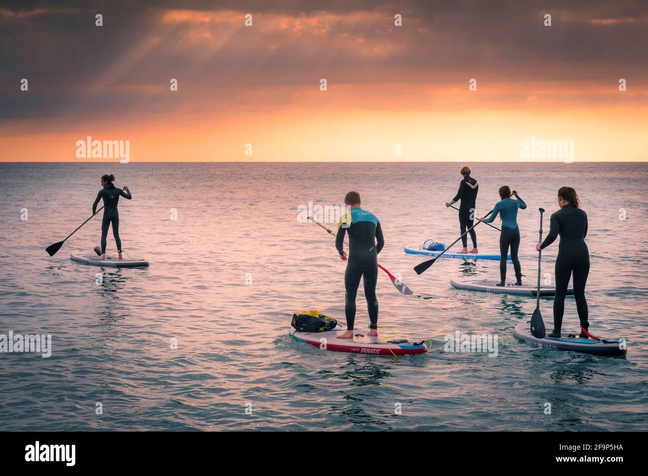Un groupe de vacanciers pagayant sur des planches à roulettes Stand Up tandis que le soleil se couche sur la baie de Fistral à Newquay, en Cornouailles. Banque D'Images