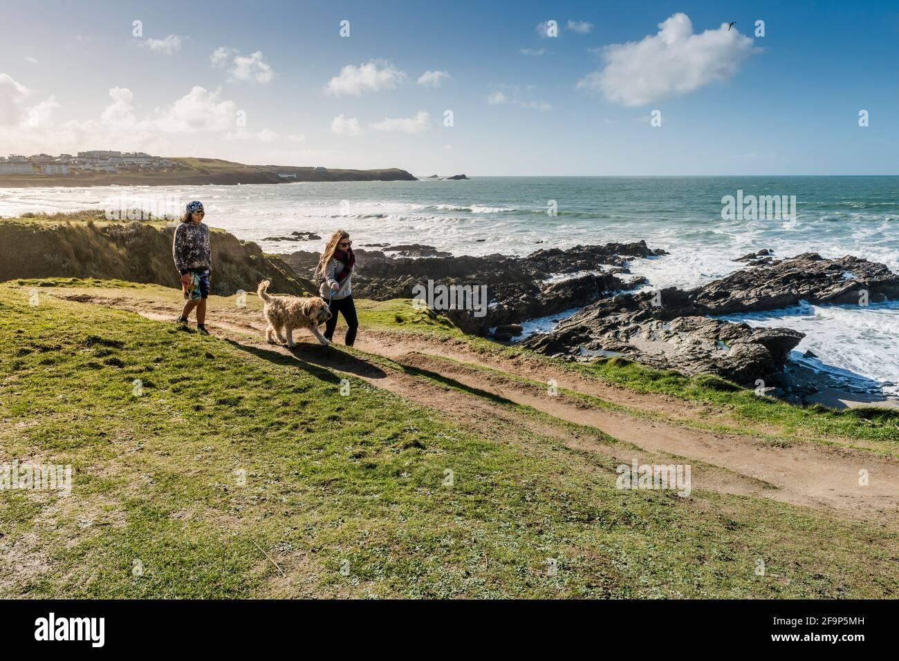Les gens qui marchent leur chien le long du sentier de la côte sur le promontoire de Newquay, en Cornouailles. Banque D'Images