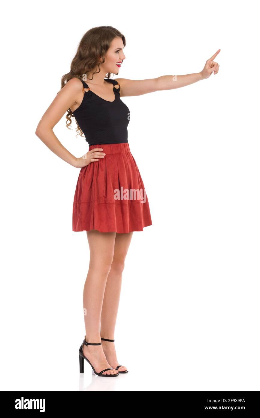 Belle jeune femme en daim brun mini jupe, haut noir et talons hauts est regarder loin et pousser quelque chose avec index doigt. Vue latérale. En entier Banque D'Images