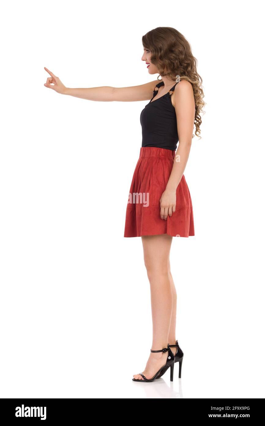 Belle jeune femme en daim brun mini jupe, noir haut et talons hauts est regarder loin et touchant quelque chose avec l'index. Vue latérale. Complet le Banque D'Images