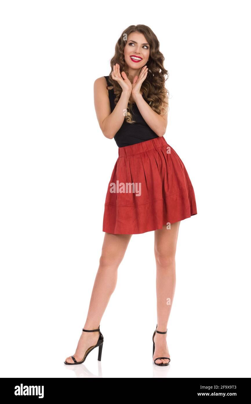 Bonne femme en daim marron mini jupe, noir haut et talons hauts est tenue la tête dans les mains, regardant loin et souriant. Vue avant. Grand studio sho Banque D'Images