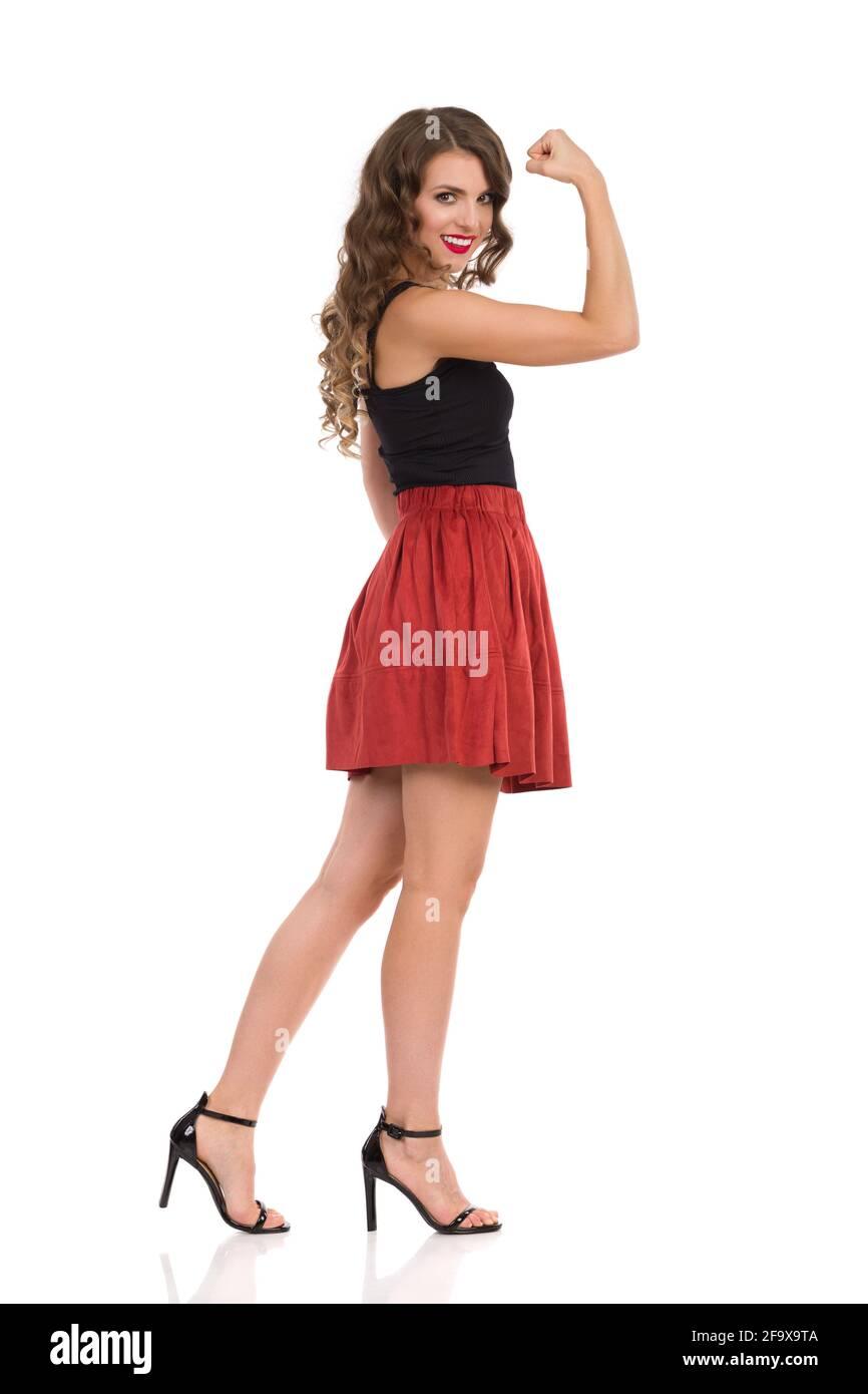 Jeune femme confiante en daim mini jupe, noir haut et talons hauts est debout, fléchissant les muscles, regardant l'appareil photo et sourire. Vue latérale. Longueur totale Banque D'Images