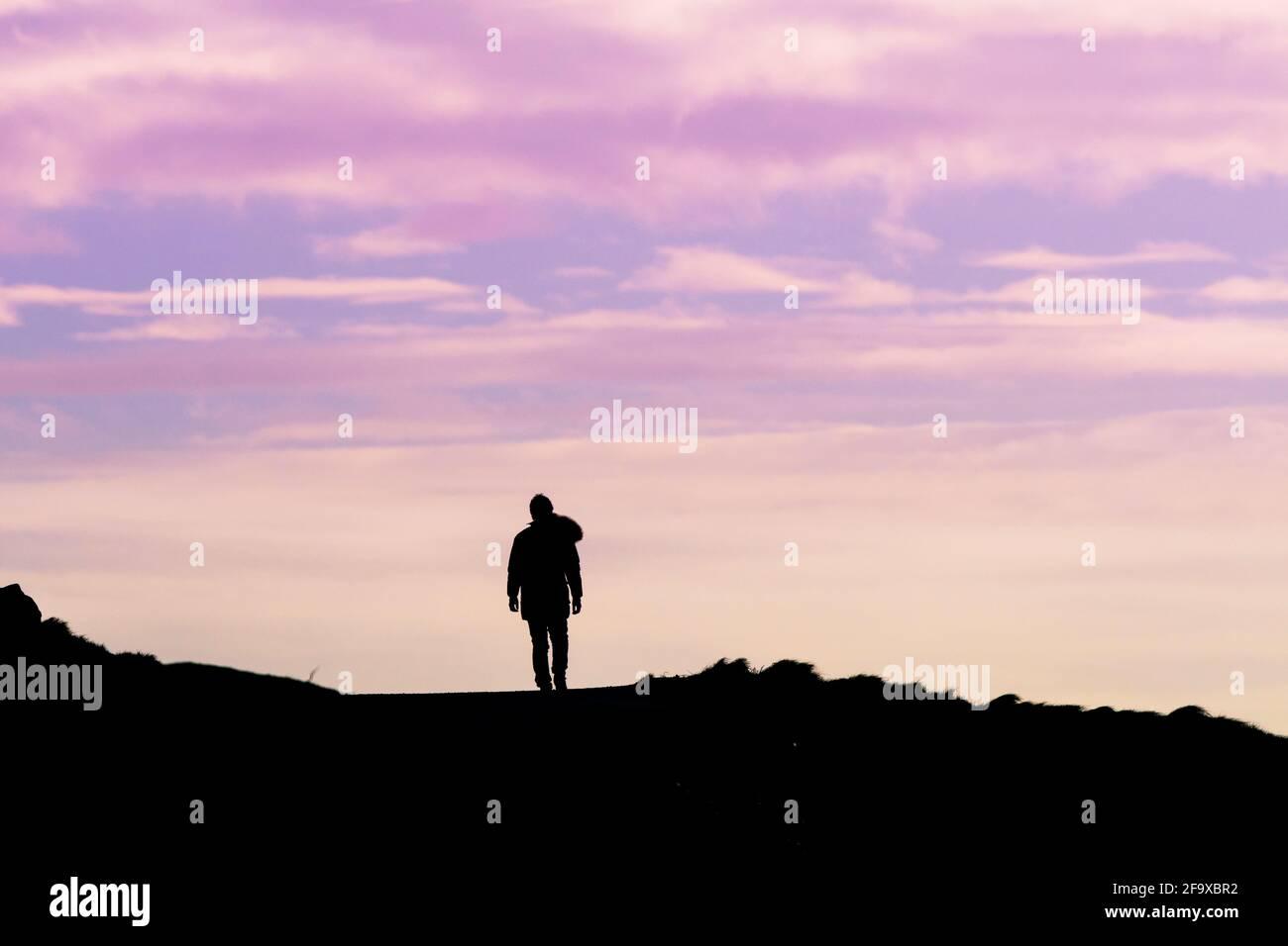 Un marcheur solitaire a taillé sur un ciel de couleur pastel. Banque D'Images
