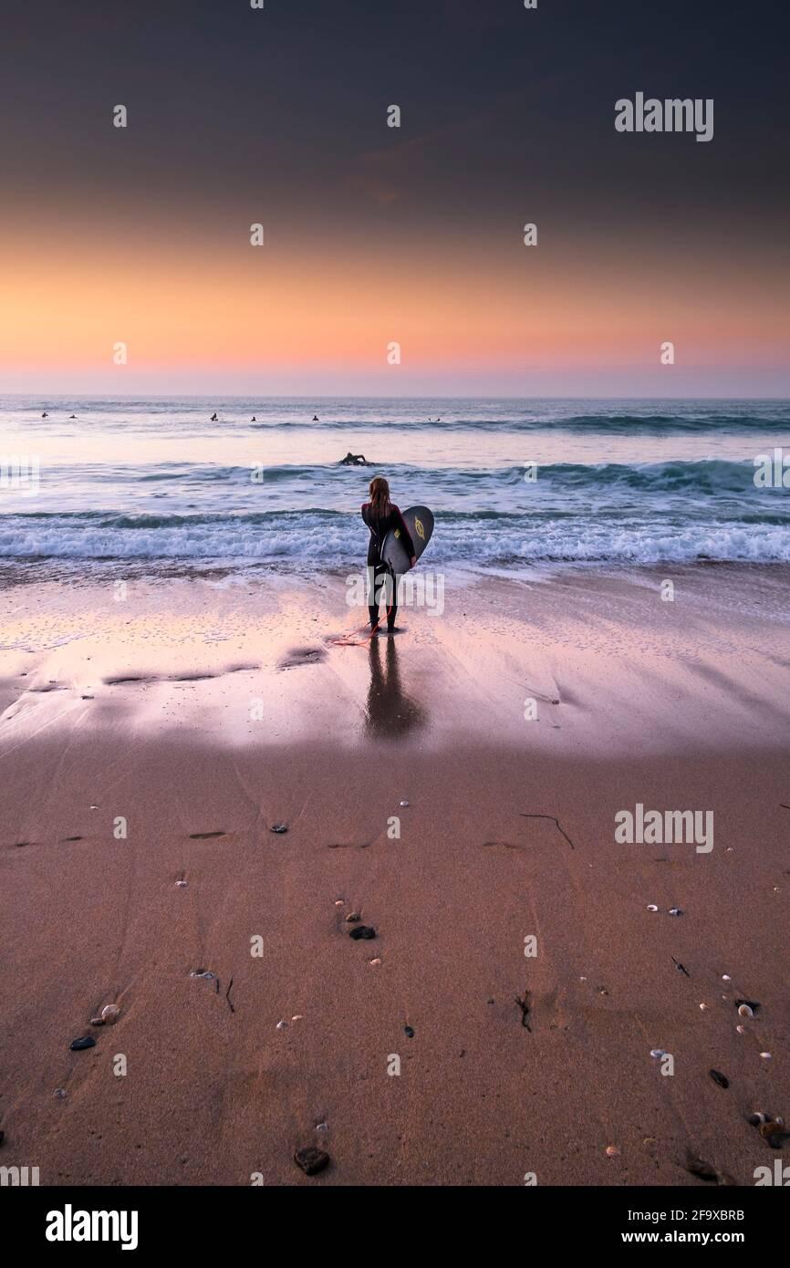 Une surfeuse femelle debout sur le rivage à la lumière du soir sur la plage de Fistral à Newquay, dans les Cornouailles. Banque D'Images