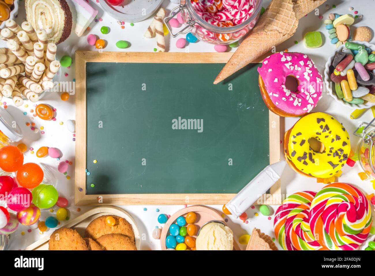 Sélection de bonbons colorés. Assortiment de bonbons, chocolats, beignets, biscuits, sucettes, vue de dessus de crème glacée sur fond blanc Banque D'Images